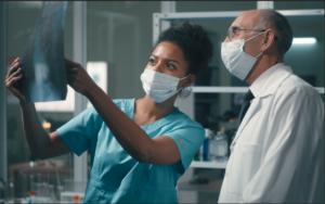 Female nurse holds up an X-ray to show male hospital staff.